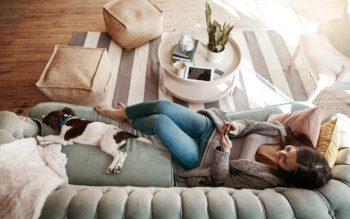 Mulher relaxando no sofá de casa com cachorro - Cidades do Quinto Andar