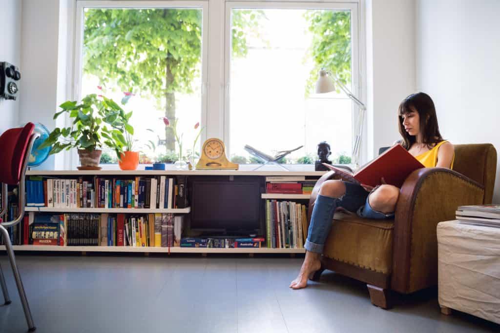 Viver sem ar condicionado - mulher lê ao lado de janela com móvel baixo