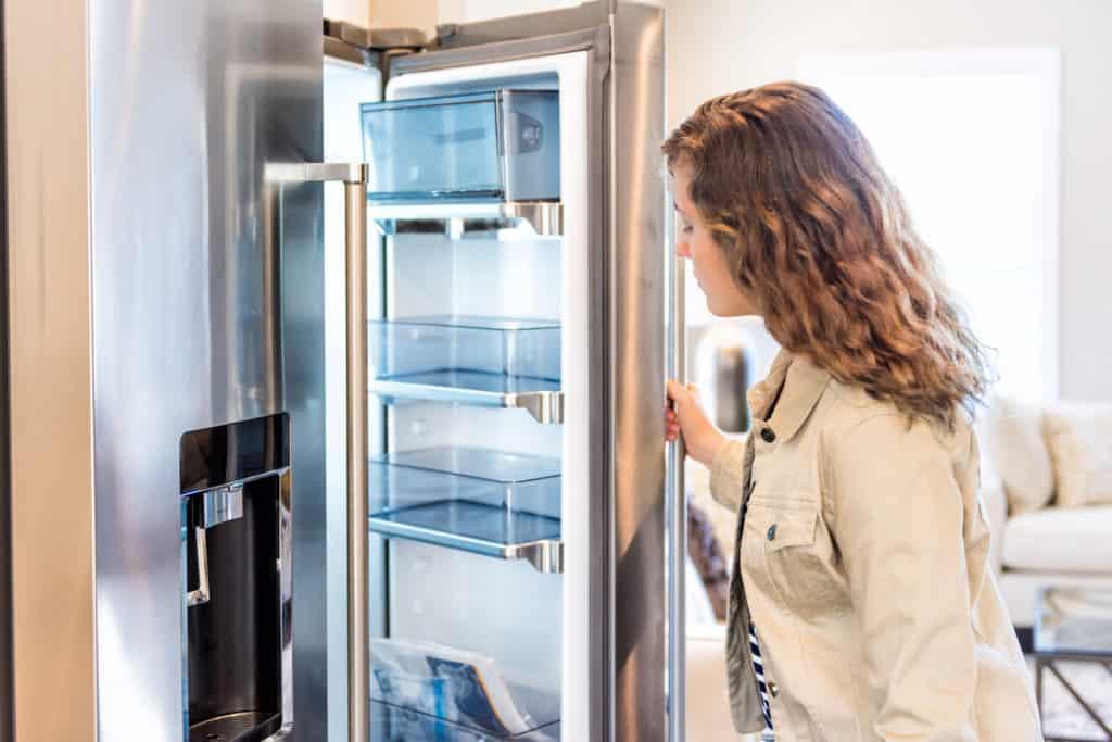 Vistoria de entrada - mulher verifica geladeira