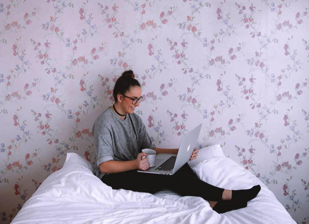 Mulher em almofada branca usando um laptop, com papel de parede ao fundo.