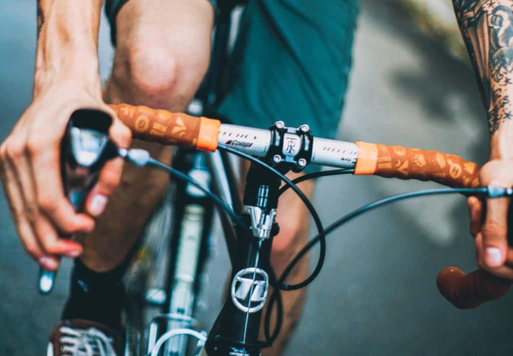 Homem pilota bicicleta com as mãos no freio