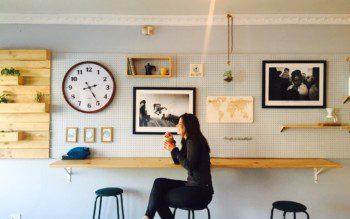 Mulher sorri diante de parede com objetos pendurados