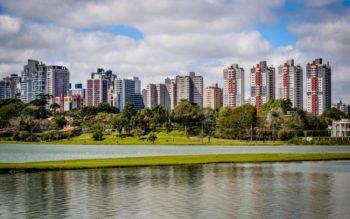 Foto que ilustra matéria sobre qualidade de vida em Curitiba mostra uma panorâmica do Parque Barigui, com um espelho d'água em primeiro plano, árvores no meio da imagem e altos prédios ao fundo