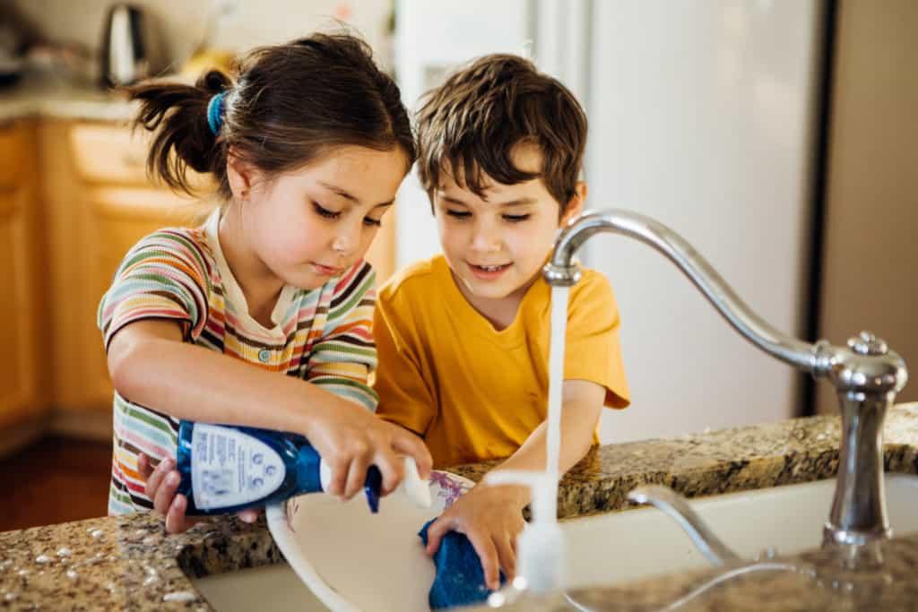 Crianças lavando louça