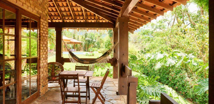 Casa para alugar - Imagem de uma varanda de uma casa com mesas, cadeiras e um gramado ao fundo