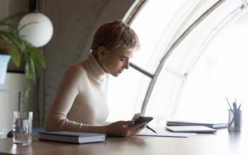 Contrato de aluguel - Mulher com celular na mão analisa documentos