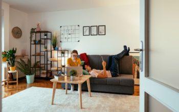 Foto que ilustra matéria sobre apartamento mobiliado para alugar mostra uma mulher e um homem em uma sala com quadros e plantas. A mulher mexe em um notebook, enquanto o homem está deitado no sofá.