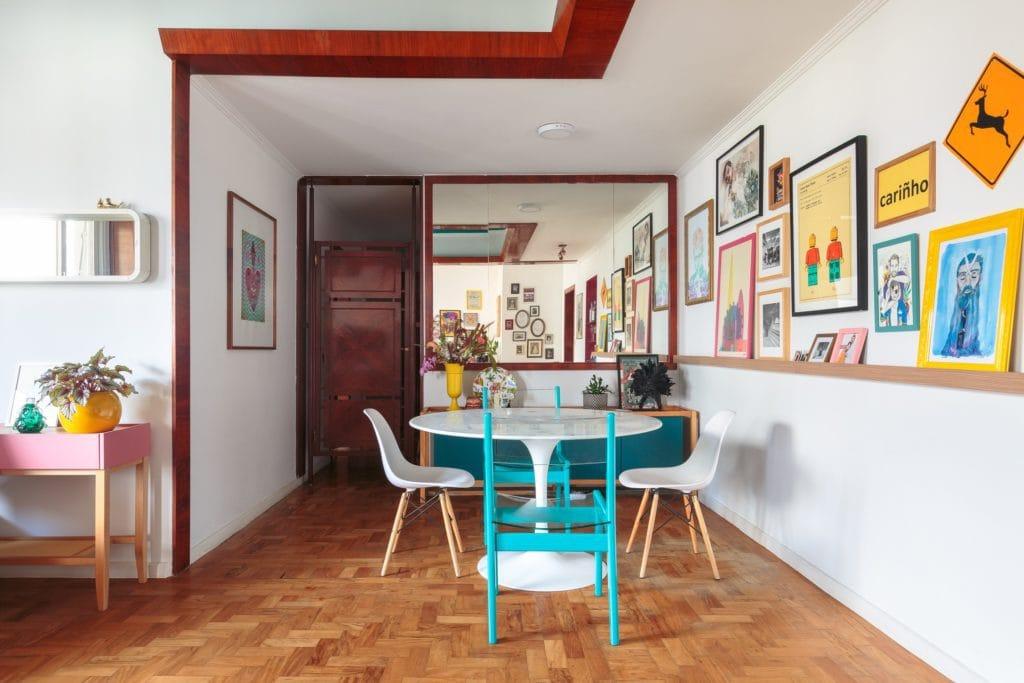 Detalhes da sala de jantar de apartamento na Avenida Paulista, com um grande espelho ao fundo, mesa e quadros na parede