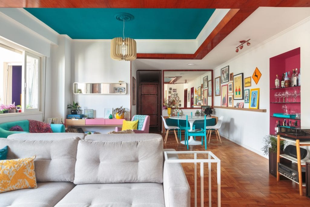 Grande sala de apartamento na Avenida Paulista, dividido entre sala de estar e sala de jantar, com sofás, mesa e itens de decoração