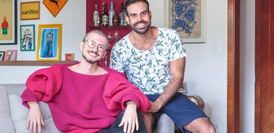 Casal formado por dois homens, sentados em um sofá e sorrindo, em um apartamento no Edifício Saint Honoré, na Avenida Paulista, em São Paulo