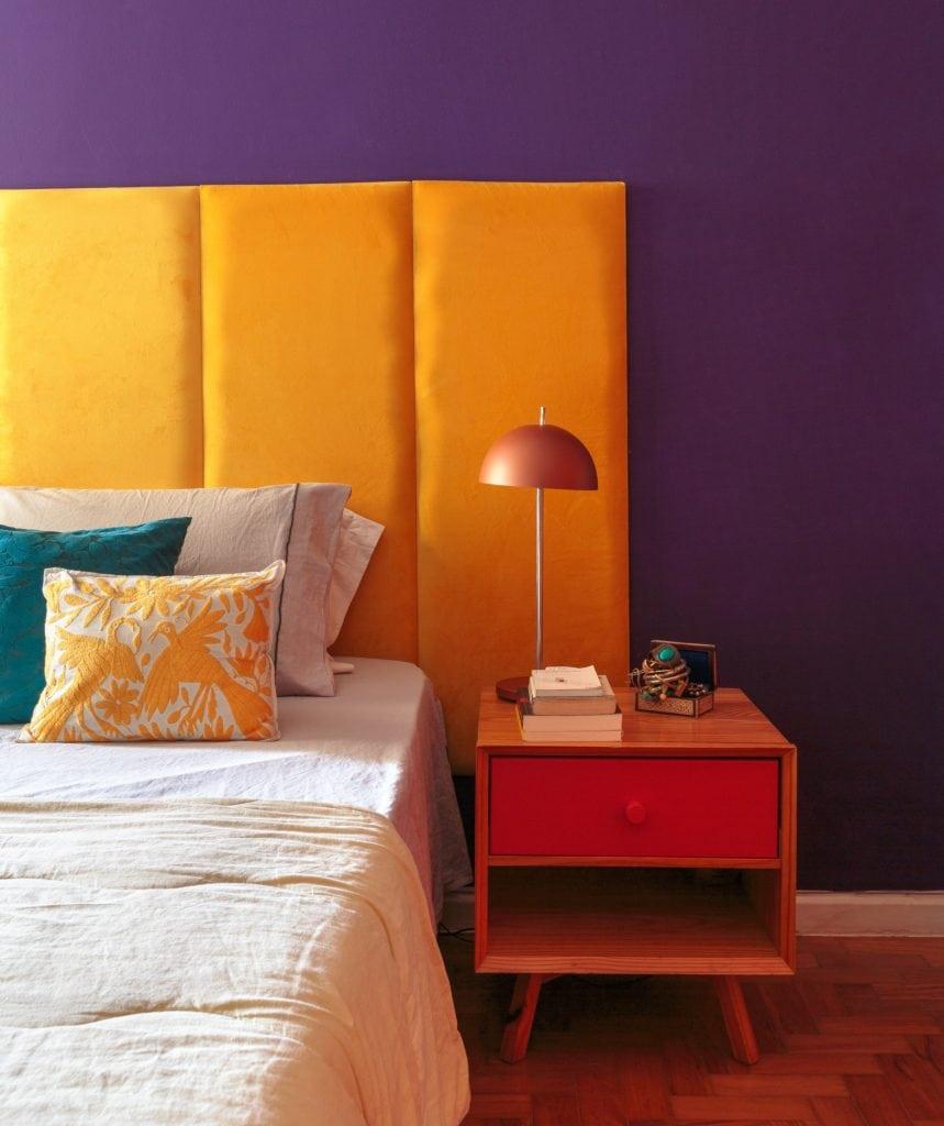 Foto com os detalhes de um quarto em apartamento do Edifício Saint Honoré. Com uma cama, uma parede roxa, cabeceira amarela e uma mesinha de cabeceira de madeira com gaveta vermelha