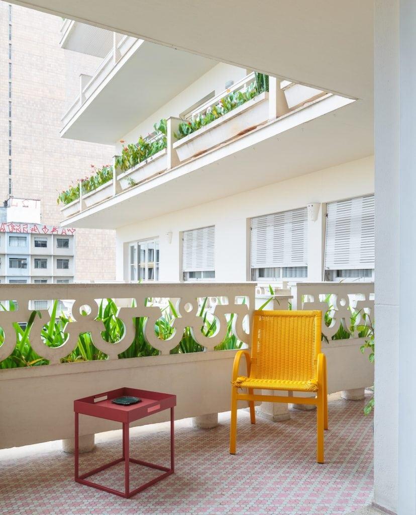 Detalhe da varanda de apartamento no Edifício Saint Honoré, na Avenida Paulista, em São Paulo, mostra uma cadeira amarela e uma mesinha de apoio vermelha