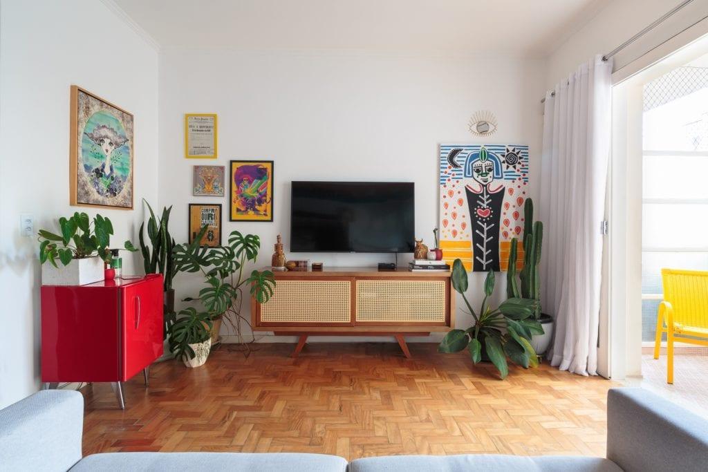 Sala de apartamento na Avenida Paulista, com quadros na parede, plantas e móveis aparadores.