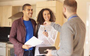 Após registro da matrícula de imóvel, casal sorridente recebe de corretor de imóveis as chaves de sua nova casa.