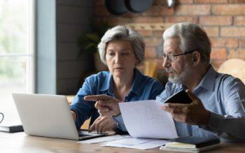 Em foto que ilustra o IPCA de maio de 2021, um casal de pessoas idosas sentados à mesa, diante de um notebook e fazendo contas