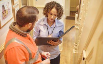 Em matéria sobre laudo de vistoria de imóvel, uma mulher com uma pasta na mão realiza uma inspeção ao lado de um eletricista