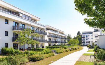Foto que ilustra matéria sobre mercado imobiliário mostra um complexo de prédios baixos, cada um com três andares, rodeados por um caminho de concreto e jardins com arbustos
