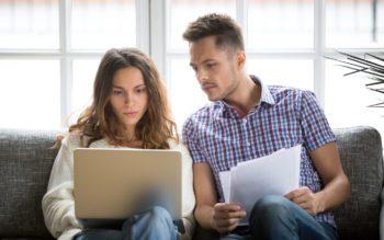 Em foto que ilustra matéria sobre modalidades de crédito para aluguel de imóveis, mulher sentada em um sofá tem um notebook em seu colo enquanto homem ao seu lado também observa a tela com alguns papéis nas mãos