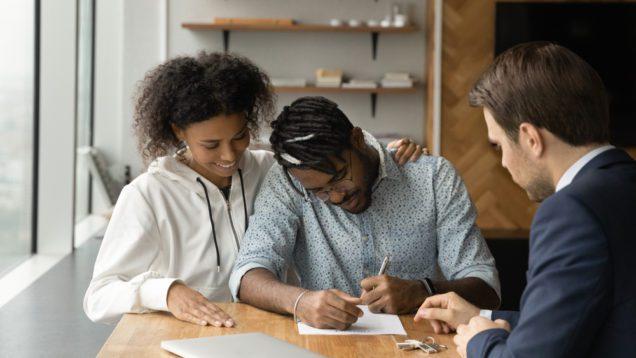 Foto que ilustra matéria sobre taxa de financiamento imobiliário mostra um casal de jovens assinando um contrato diante de um homem de terno