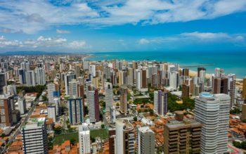 Foto que ilustra matéria sobre o custo de vida em Fortaleza mostra os prédios da cidade com o mar azul ao fundo.