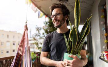 Em foto que ilustra um teste de personalidades sobre plantas em casa, um homem segura um vaso com uma planta da espécie espada de São Jorge.