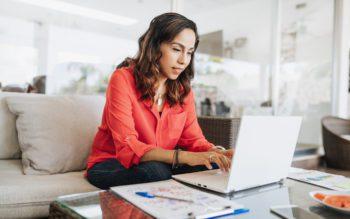 """Em foto que ilustra o quiz """"Você sabe quanto custa essa casa?"""", uma mulher sentada em um sofá usa um laptop posicionado em uma mesa de centro, ao lado de um bloco de anotações com uma caneta em cima."""