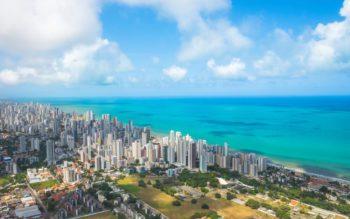 Foto que ilustra matéria sobre os melhores bairros de Recife mostra a cidade vista do alto, com muitos prédios no canto esquerdo da imagem e um mar azul cristalino mais à direita.