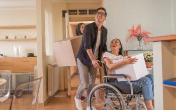 Três pessoas entrando em uma sala de uma casa, carregando caixas e mudanças após fechar o contrato de moradia por assinatura.