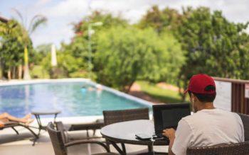 Homem usando computador sentado diante de uma piscina