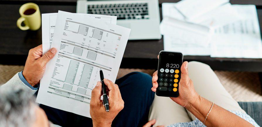 Foto que ilustra matéria sobre composição de renda para aluguel mostra, de um ângulo visto de cima, as mãos de uma pessoa segurando papeis com diversas tabelas com números impressos, enquanto outra mão segura uma calculadora