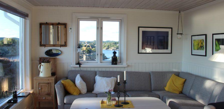 Imagem de uma sala de estar com um sofá em L da cor cinza. As paredes são decoradas com vários quadros e há uma mesa de centro de madeira com flores em cima. No sofá há almofadas coloridas. Exemplo de como usar sofá em L.
