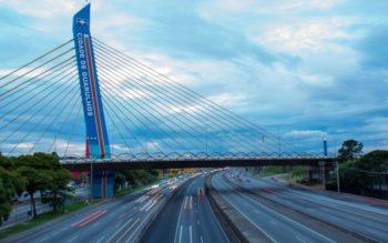 Imagem de uma estrada, com três vias duplas, passando por baixo de um portal/passarela com o escrito Cidade de Guarulhos, capa do post de melhores bairros de Guarulhos