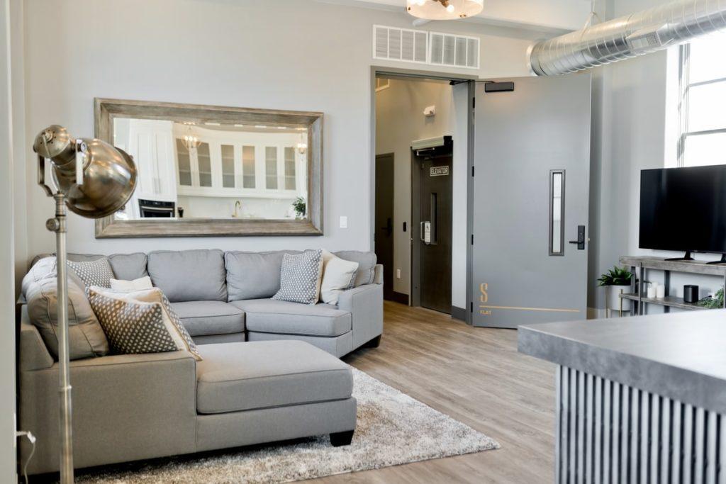 Sala de televisão. Um sofá em L no canto, acima de um tapete, com uma lâmpada na lateral direita e uma porta para um corredor na lateral esquerda. Na parede do fundo da imagem, acima do sofá, há um quadro.