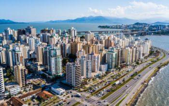 Foto que ilustra matéria sobre custo de vida em Florianópolis mostra uma visão aérea de vários prédios da cidade à beira-mar em um dia ensolarado, com uma ponte ao fundo.