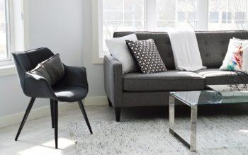 Imagem que ilustra matéria sobre decoração modernista mostra o detalhe de uma sala com uma poltrona preta, metade de um sofá cinza escuro com almofadas em cima e parte de uma mesa de centro de tampo de vidro sobre um tapete