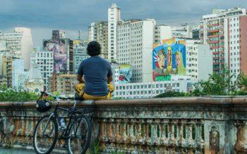 Foto que ilustra matéria sobre grafite em BH mostra o mirante da Rua Sapucaí, localizada no Centro da Cidade, de onde se vê ao fundo diversos prédios, alguns deles com artes coloridas pintadas em suas fachadas ou laterais. Sobre a mureta, com uma bicicleta encostada, um homem sentado de costas e de pernas cruzadas observa as obras de arte.