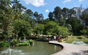 foto do parque celso daniel, na cidade de santo andré. Mulher e homem caminham perto de lago, com fontes, cercado pela mata