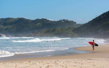 Foto que ilustra matéria sobre as praias de Florianópolis mostra um surfista de pé na areia, à direita da tela, com uma prancha de surfe debaixo do braço olhando para o mar na Praia da Galheta
